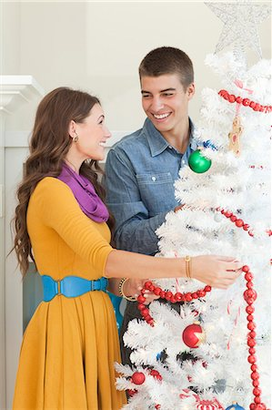 Young couple decorating Christmas tree Stock Photo - Premium Royalty-Free, Code: 640-06963427