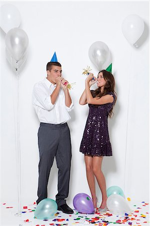 Young couple blowing horns at party Stock Photo - Premium Royalty-Free, Code: 640-06963492