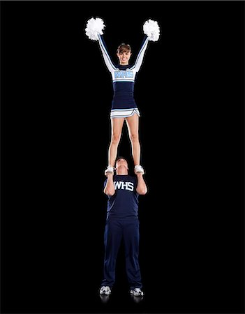 Teenage sportsman(16-17) holding aloft teenage cheerleader girl (16-17) Stock Photo - Premium Royalty-Free, Code: 640-06963614