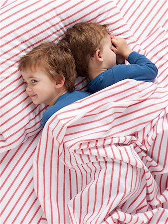 USA, Utah, Orem, Twin boys (2-3) wearing pajamas lying on bed Stock Photo - Premium Royalty-Free, Code: 640-06963758
