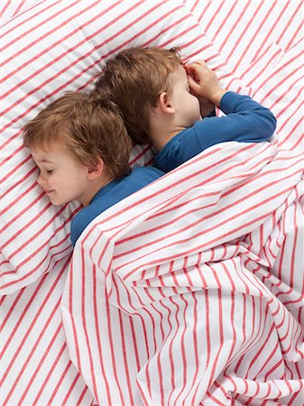 USA, Utah, Orem, Twin boys (2-3) wearing pajamas lying on bed Stock Photo - Premium Royalty-Free, Code: 640-06963759