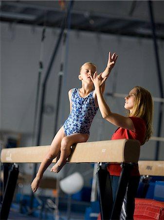 preteen girls stretching - USA, Utah, Orem, coach assisting girl gymnast (10-11) on balance beam Stock Photo - Premium Royalty-Free, Code: 640-08089047