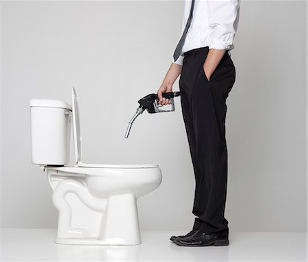 Studio shot of businessman pouring fuel into toilet Stock Photo - Premium Royalty-Free, Code: 640-08546045