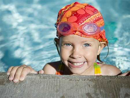 Portrait of a girl leaning at the edge of a swimming pool Stock Photo - Premium Royalty-Free, Code: 640-01348405