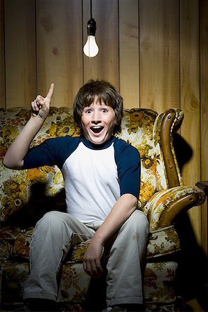 Boy sitting on sofa with light bulb idea Stock Photo - Premium Royalty-Free, Code: 640-01348527
