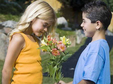 Profile of a boy giving flowers to a girl Stock Photo - Premium Royalty-Free, Code: 640-01348751