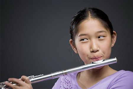 Close-up of a girl playing the flute Stock Photo - Premium Royalty-Free, Code: 640-01348770