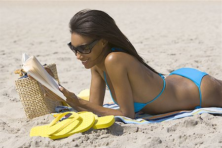 Profile of a young woman reading on the beach Stock Photo - Premium Royalty-Free, Code: 640-01348822