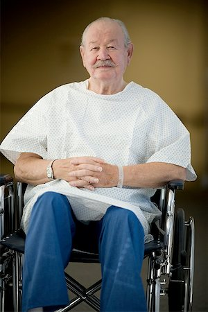 Male patient sitting in a wheelchair with his hands clasped Stock Photo - Premium Royalty-Free, Code: 640-01348899