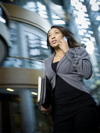 Businesswoman using a mobile phone and carrying files Stock Photo - Premium Royalty-Free, Code: 640-01348908