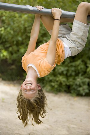 Portrait of a girl hanging upside down from a jungle gym Stock Photo - Premium Royalty-Free, Code: 640-01348953