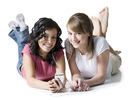 Portrait of two girls listening to music on an MP3 player Stock Photo - Premium Royalty-Free, Code: 640-01349312