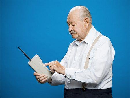 Older man making call on retro wireless phone Stock Photo - Premium Royalty-Free, Code: 640-01349498