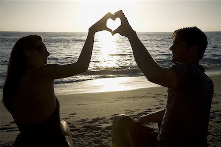 female silhouettes heart - Couple on a beach making a heart symbol with their hands Stock Photo - Premium Royalty-Free, Code: 640-01349804