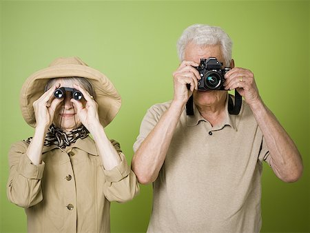 Close-up of an elderly woman looking through a pair of binoculars with an elderly man taking a picture Stock Photo - Premium Royalty-Free, Code: 640-01349837