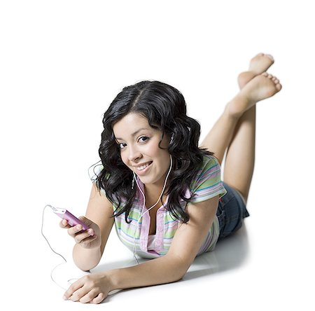 Portrait of a teenage girl listening to an Mp3 player Stock Photo - Premium Royalty-Free, Code: 640-01349856
