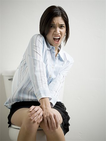Portrait of a young woman sitting on a toilet Stock Photo - Premium Royalty-Free, Code: 640-01349852
