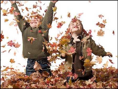 pile leaves playing - Young children playing in pile of fallen leaves Stock Photo - Premium Royalty-Free, Code: 640-01349989