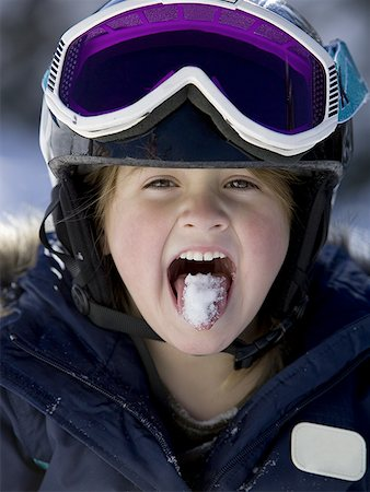 Young girl in winter with snow on tongue and ski goggles Stock Photo - Premium Royalty-Free, Code: 640-01354218