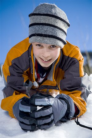 Portrait of a boy lying in snow Stock Photo - Premium Royalty-Free, Code: 640-01354260