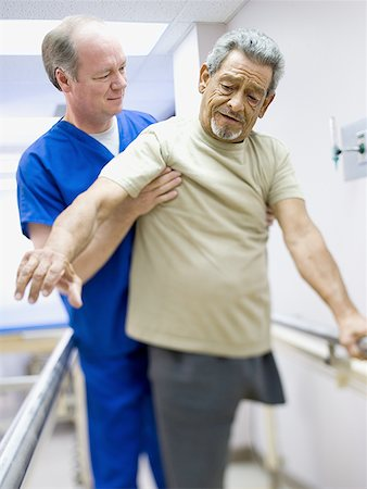 Male doctor assisting a physically challenged senior man on a treadmill Stock Photo - Premium Royalty-Free, Code: 640-01354587