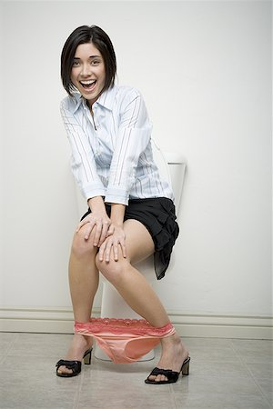 Portrait of a young woman sitting on a toilet with her hand on her knee Stock Photo - Premium Royalty-Free, Code: 640-01354681