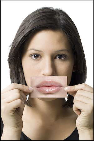 female silhouette head and hand - Close-up of a young woman holding a photograph of lips in front her mouth Stock Photo - Premium Royalty-Free, Code: 640-01355095