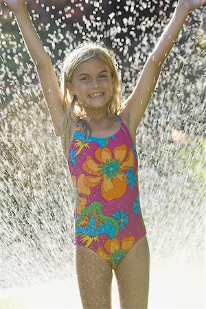 Portrait of a girl with her hands raised in a spray of water Stock Photo - Premium Royalty-Free, Code: 640-01355111