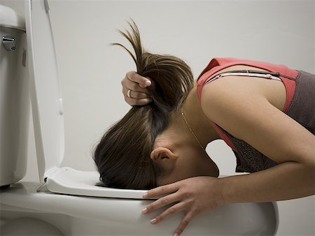 Profile of a young woman vomiting into a toilet bowl Stock Photo - Premium Royalty-Free, Code: 640-01355401