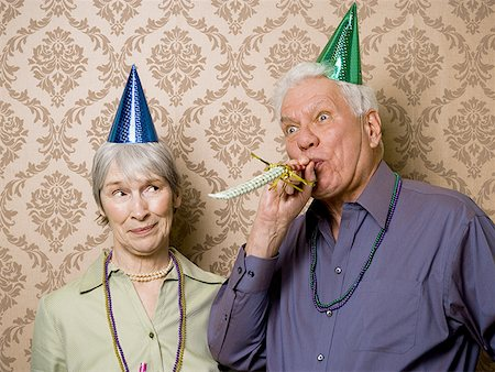 A senior man standing with a senior woman and blowing a party favor Stock Photo - Premium Royalty-Free, Code: 640-01355600