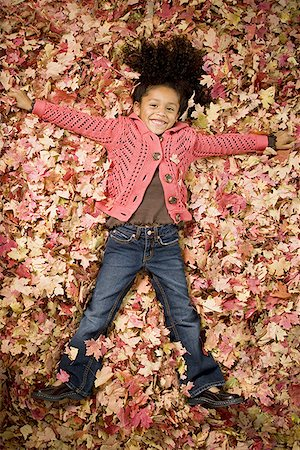 pile leaves playing - Young girl playing in fallen leaves Stock Photo - Premium Royalty-Free, Code: 640-01355877