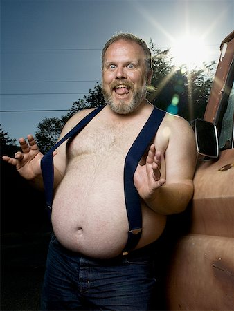 Overweight man with suspenders by truck Stock Photo - Premium Royalty-Free, Code: 640-01355905