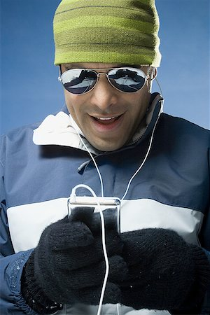 Close-up of a mid adult man watching his portable video player Stock Photo - Premium Royalty-Free, Code: 640-01356067