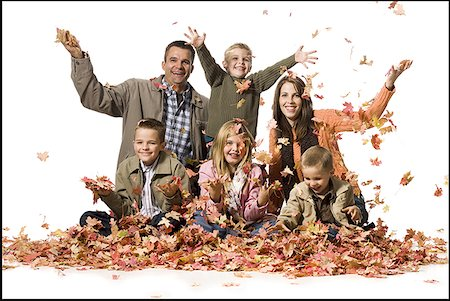 pile leaves playing - Family posing in a pile of fallen leaves Stock Photo - Premium Royalty-Free, Code: 640-01356106