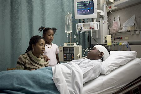Mother and her daughter looking at a teenage boy in the hospital Stock Photo - Premium Royalty-Free, Code: 640-01356188