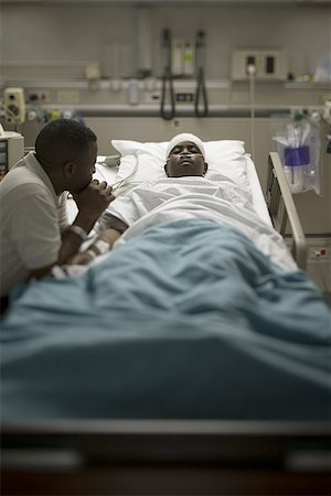 Profile of a father sitting beside his son lying on a hospital bed Stock Photo - Premium Royalty-Free, Code: 640-01356308