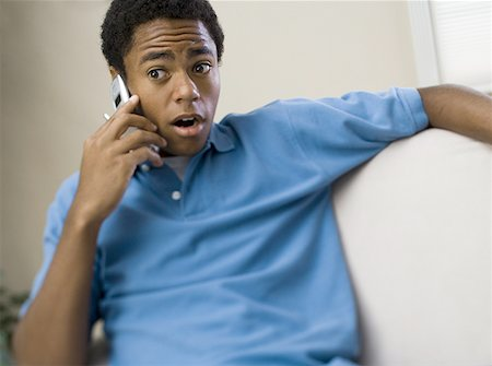 Teenage boy on a mobile phone with his mouth open Stock Photo - Premium Royalty-Free, Code: 640-01356454
