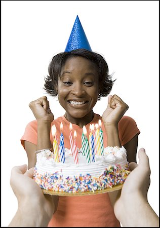 Close-up of a young woman looking at a birthday cake Stock Photo - Premium Royalty-Free, Code: 640-01356539