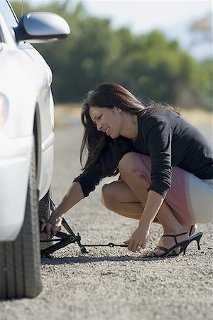 Profile of a woman fixing a flat tire Stock Photo - Premium Royalty-Free, Code: 640-01356595