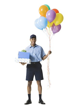 Young man carrying gift boxes while holding balloons Stock Photo - Premium Royalty-Free, Code: 640-01356614