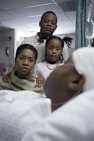 Parents and their daughter looking at a teenage boy in the hospital Stock Photo - Premium Royalty-Free, Code: 640-01356636