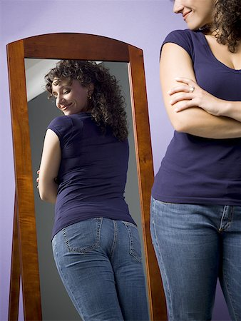 Young woman looking at her buttocks in the mirror Stock Photo - Premium Royalty-Free, Code: 640-01356660