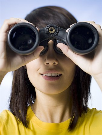 Close-up of a young woman looking through a pair of binoculars Stock Photo - Premium Royalty-Free, Code: 640-01356698