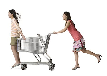Profile of a young woman pushing a teenage girl in a shopping cart Stock Photo - Premium Royalty-Free, Code: 640-01356884