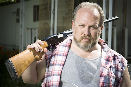 Overweight man with a shotgun Stock Photo - Premium Royalty-Free, Code: 640-01357322