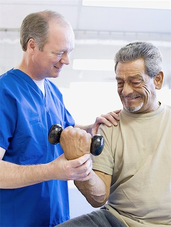Low angle view of a male doctor assisting a physically challenged senior man undergo physical therapy Stock Photo - Premium Royalty-Free, Code: 640-01357684