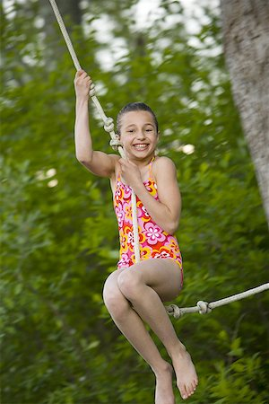 Portrait of a girl swinging on a rope Stock Photo - Premium Royalty-Free, Code: 640-01357856