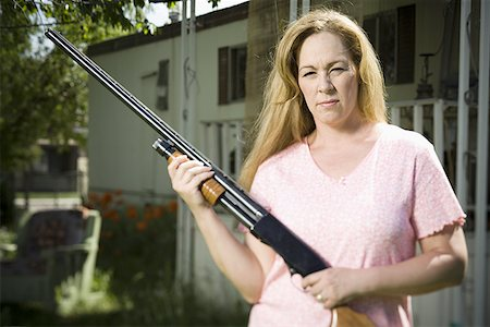 Woman in trailer park with shotgun Stock Photo - Premium Royalty-Free, Code: 640-01357952