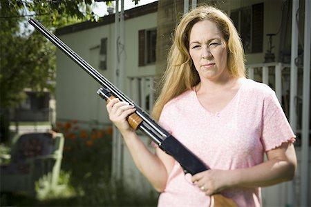 Woman in trailer park with shotgun Stock Photo - Premium Royalty-Free, Code: 640-01357952