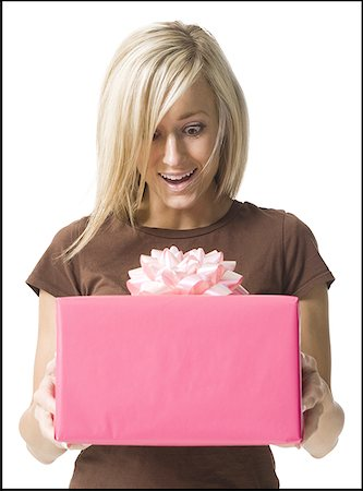 Young woman looking at a gift in her hands Stock Photo - Premium Royalty-Free, Code: 640-01358032